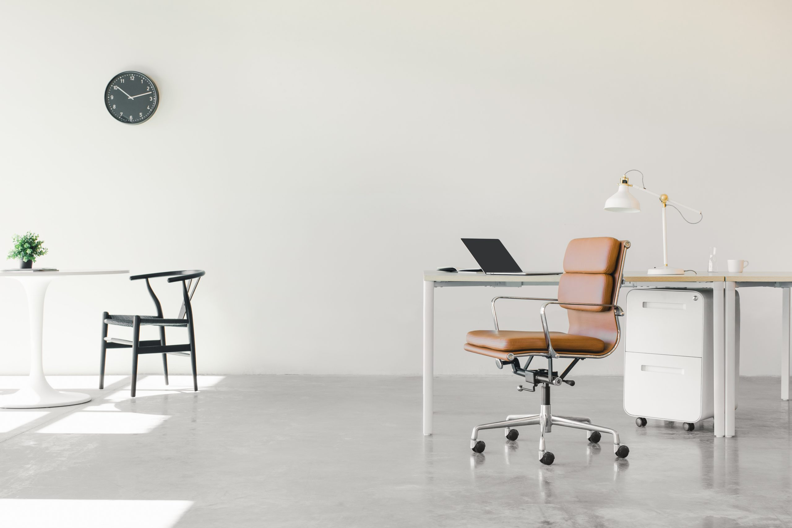 An open floor plan office space with a minimalist setup of chairs and desks.